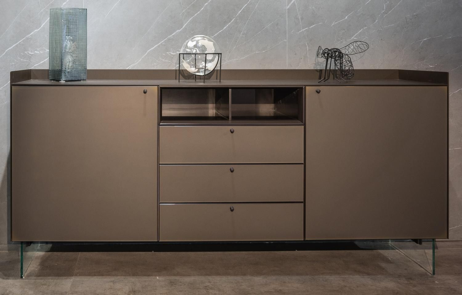 Cabinet STEK. Aluminum profile Dark Brown Matt Color. The facade of the Rim, glass Colour Matt 07. Table top and sides Champagne Satin Grey. Dark Brown Matt Color niche. Grey Trasparent shelves. Thuja Scuro interior filling. The legs are made of glass.